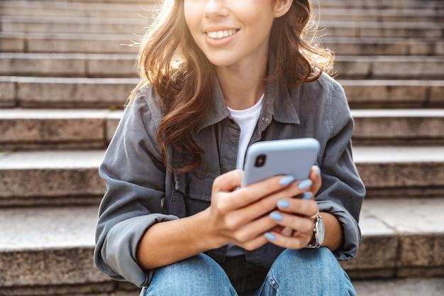 Ragazza allegra seduta sulle scale all'aperto, usando il telefono cellulare