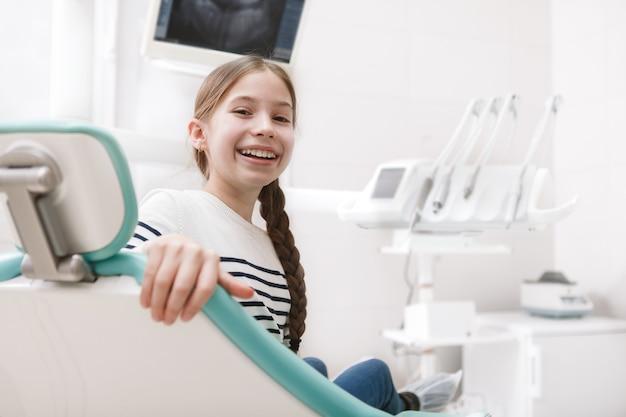 Allegro giovane ragazza sorridente alla telecamera, seduto in poltrona odontoiatrica, copia dello spazio