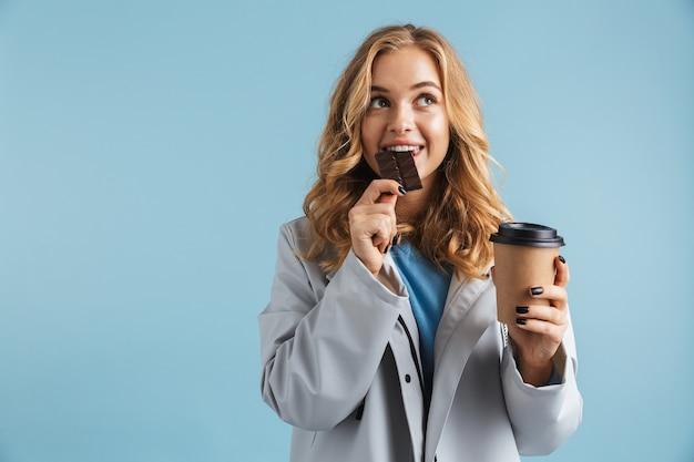 Ragazza allegra che indossa un impermeabile in piedi isolato, mangiare cioccolato, bere caffè