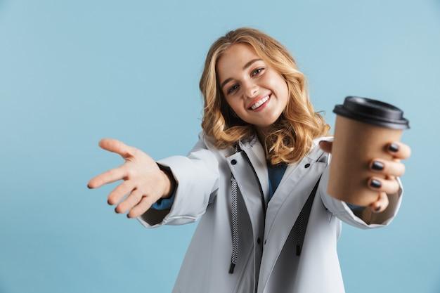 Giovane ragazza allegra che indossa un impermeabile in piedi isolato, mostrando la tazza di caffè