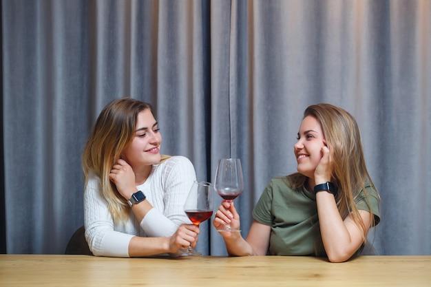 Giovani amiche allegre con gli occhiali a tavola a casa