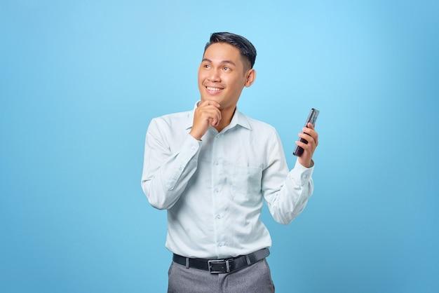 Allegro giovane uomo d'affari bello che tiene smartphone e alza lo sguardo su sfondo blu
