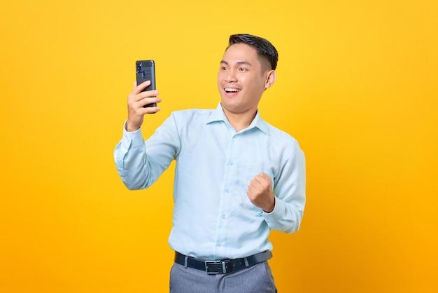 Allegro giovane uomo d'affari bello che usa lo smartphone e fa il gesto di vittoria su sfondo giallo