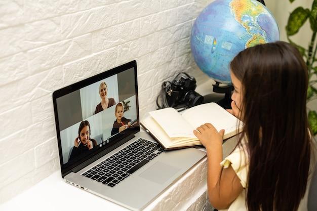 Allegri bambine che usano il computer portatile, studiano attraverso il sistema di e-learning online