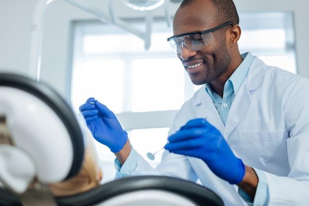 Allegro giovane dentista maschio esaminando i suoi piccoli denti di pazienti con uno specchio della bocca e una sonda e sorridendole