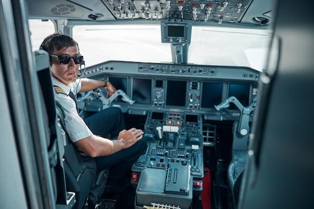 Un giovane allegro in uniforme da aereo e occhiali vicino al controllo si sta preparando per il jet in volo
