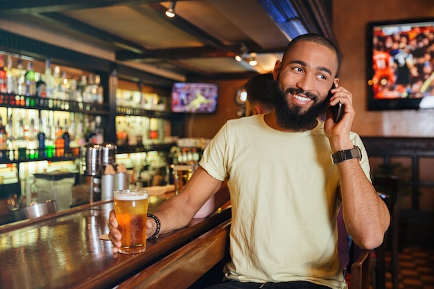 Giovane allegro che beve birra e parla al cellulare in pub