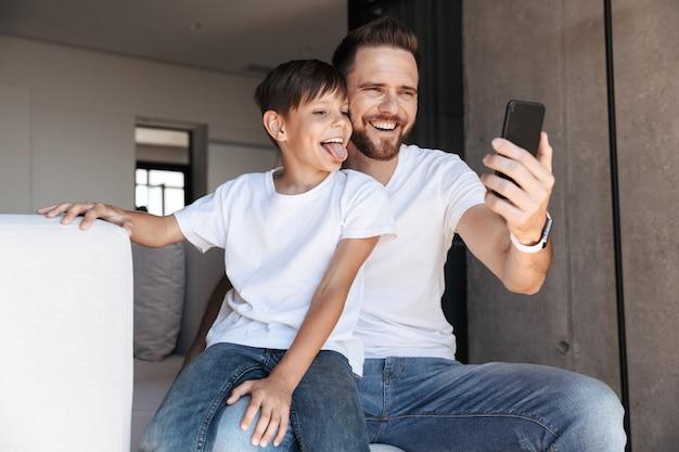 Allegro giovane padre papà utilizzando il telefono cellulare con il figlio
