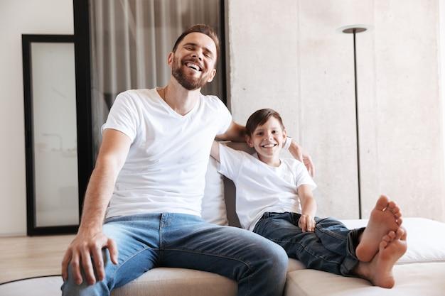 Allegro giovane padre papà guardando la tv con il figlio.
