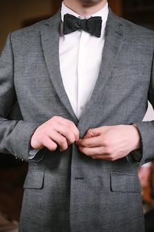 Il giovane allegro in un vestito grigio tocca una giacca