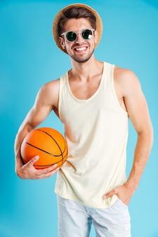 Giovane allegro in cappello e occhiali da sole che tengono la palla da basket