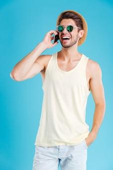 Giovane allegro in cappello e occhiali da sole in piedi e parlando al cellulare sopra la parete blu