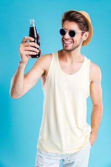 Giovane allegro in cappello e occhiali da sole con una bottiglia di soda sul muro blu