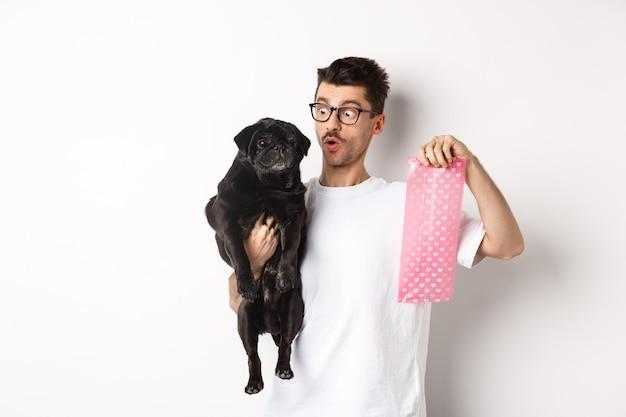 Giovane allegro che tiene il carlino nero e il sacchetto rosa della cacca di cane, levantesi in piedi sopra il bianco
