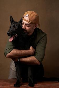 Giovane allegro che abbraccia il suo cane, ritratto all'interno