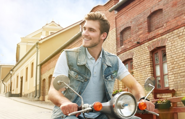 Il giovane allegro sta guidando sul motorino in città.