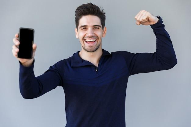 Giovane allegro che mostra il telefono cellulare dello schermo in bianco mentre levandosi in piedi isolato sopra gray