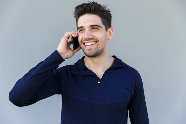 Allegro giovane uomo parla al telefono cellulare isolato su grigio