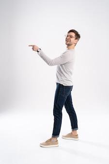 Allegro giovane uomo che indossa abiti casual isolato su sfondo bianco