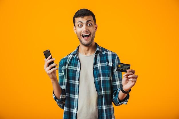 Allegro giovane uomo che indossa la camicia a quadri in piedi isolato su sfondo arancione, tenendo il telefono cellulare, mostrando la carta di credito in plastica