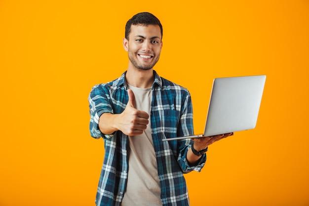 Allegro giovane uomo che indossa la camicia a quadri in piedi isolato su sfondo arancione, utilizzando il computer portatile, dando pollice in alto