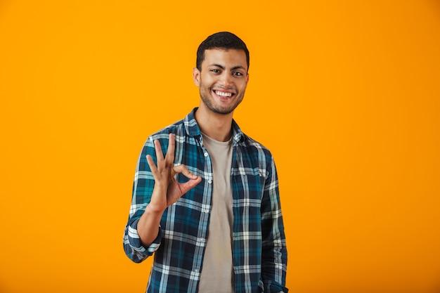 Giovane allegro che indossa la camicia a quadri in piedi isolato sopra la parete arancione, mostrando ok