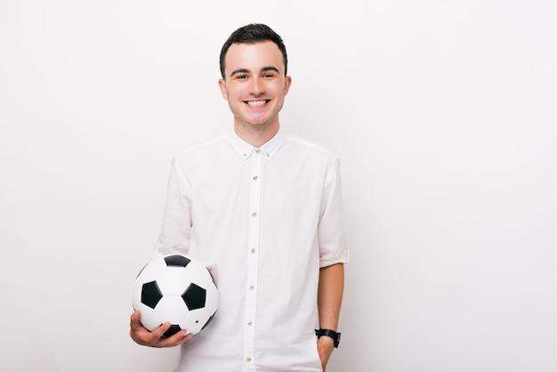 Giovane allegro in camicia bianca che tiene un pallone da calcio e che esamina la macchina fotografica felice su fondo bianco
