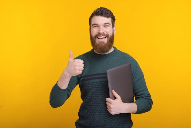 Il giovane allegro con la barba che mostra i pollici aumenta il gesto e la tenuta del suo computer portatile
