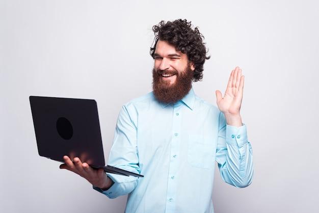 Giovane allegro con la barba che parla con qualcuno in linea, lavora a casa