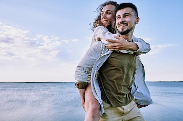 Giovane allegro con un sorriso a trentadue denti che tiene la moglie o la fidanzata sulla schiena mentre in piedi contro l'acqua e il cielo nuvoloso