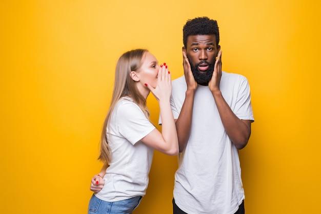 Allegra giovane coppia mista che sussurra segreto dietro la sua mano condividendo notizie in posa isolata sul muro giallo