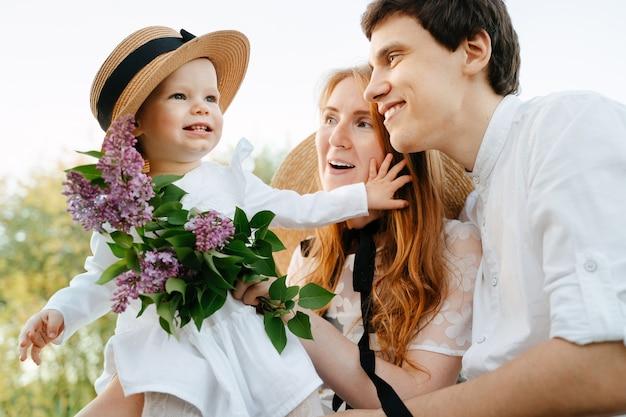 Allegro giovane madre e padre con fiori che giocano con il bambino carino il giorno del fine settimana estivo in campagna. bambina in un cappello e lilla.