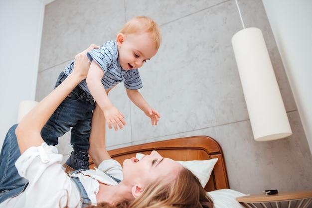 Giovane madre allegra che ride e gioca con il suo piccolo figlio sul letto