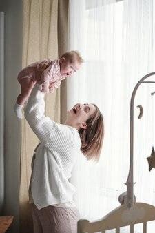 Giovane madre allegra che gioca con la sua bambina carina