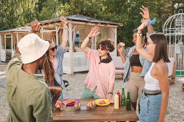 Giovani allegri che ballano con le braccia alzate al tavolo con snack