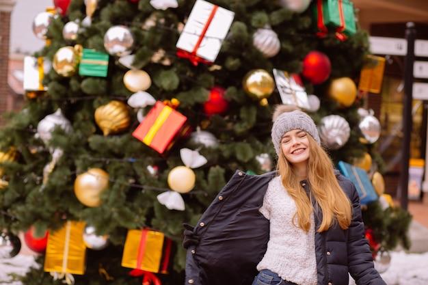 Allegra giovane donna dai capelli rossi che indossa abiti invernali, in posa sullo sfondo di un abete natalizio
