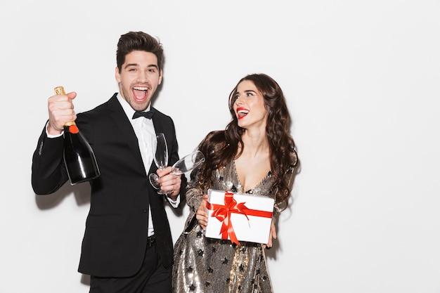 Allegro giovane coppia elegantemente vestita che celebra la festa di capodanno isolato su bianco, tenendo presente la scatola, champagne con bicchieri
