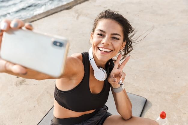 Allegro giovane sportiva che riposa dopo l'allenamento in spiaggia, prendendo un selfie, acqua potabile, seduto su un tappetino fitness