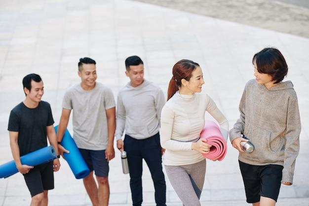 Giovani vietnamiti sportivi allegri con stuoie di yoga che tornano a casa dopo l'allenamento all'aperto