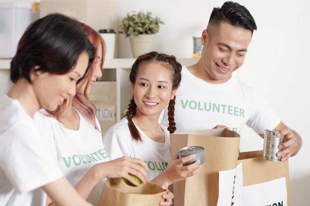 Giovani volontari vietnamiti allegri che confezionano cibo in scatola in confezioni di carta per le persone che hanno sofferto di disastri naturali