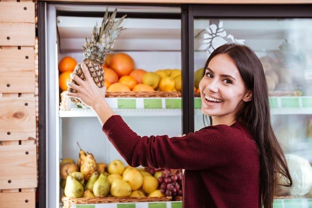 Giovane donna allegra che sceglie e compra ananas nel negozio di alimentari