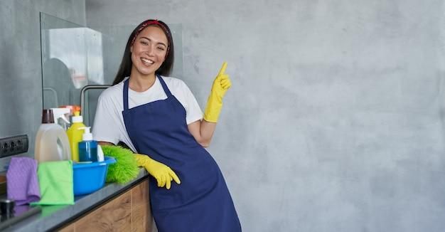Allegra giovane donna delle pulizie in guanti protettivi che sorride alla telecamera rivolta verso l'alto stando in piedi