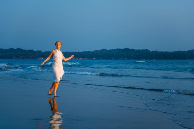 Giovane donna allegra che balla sulla sabbia bagnata, facendo gesti