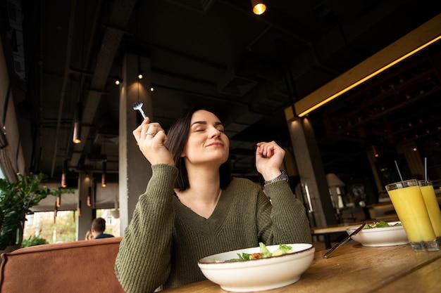 La giovane donna allegra gode dell'insalata nella caffetteria. concetto di stile di vita sano.