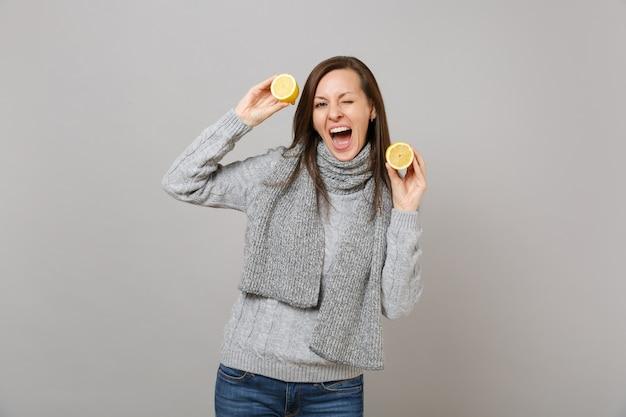 Allegra giovane donna in maglione grigio, sciarpa lampeggiante, tenendo i limoni isolati su sfondo grigio in studio. stile di vita sano, persone sincere emozioni, concetto di stagione fredda. mock up copia spazio.