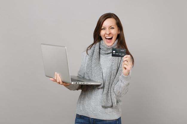 Giovane donna allegra in maglione grigio, sciarpa che lavora al computer del pc portatile che tiene la carta bancaria di credito isolata sul fondo grigio della parete. consulenza per il trattamento online di uno stile di vita sano, concetto di stagione fredda.