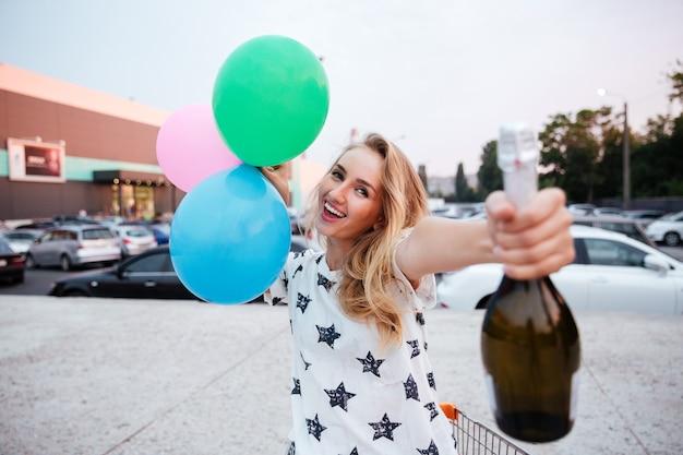 Giovane donna allegra che tiene in mano una bottiglia di champagne e palloncini e fa una festa