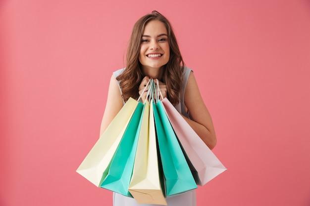 Giovane donna allegra che tiene i sacchetti della spesa.