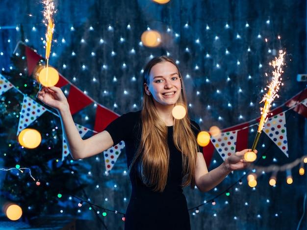 Allegro giovane donna con sparkler in mano.