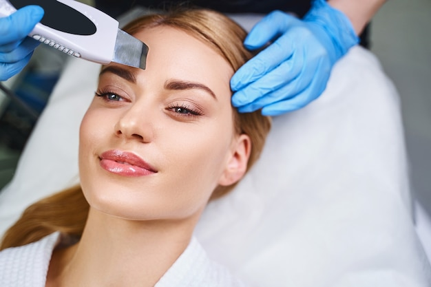 La giovane donna allegra sta visitando il salone di bellezza per ottenere il viso ad ultrasuoni da un cosmetologo esperto in guanti sterili